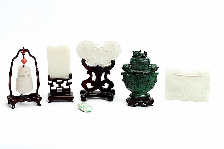 A COLLECTION OF CHINESE JADE AND MALACHITE CARVINGS. 19th / 20th Century. Comprising a malachite vase and cover, the body incised with taotie masks, lion head handles and a lion dog finial, fitted wooden stand, 10.5cm H, a white jade bell hung on a wooden stand, 11cm H, a butterfly form pendant on a stand, 10cm H, a lock-form pendant, 6 x 8cm, a Zi Gan rectangular pendant on a wooden stand, 10cm H, and a jadeite pendant, 3cm long. (6) 19-20?? ??????
