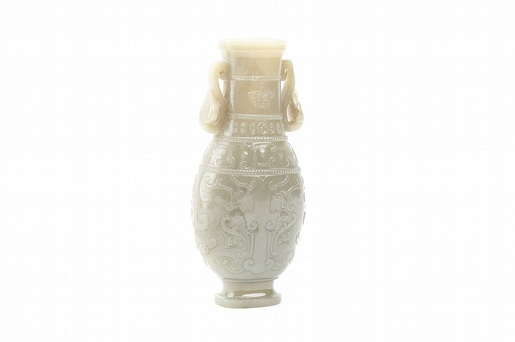 A CHINESE CELADON JADE VASE. Qing Dynasty, 18th / 19th Century. The compressed pear shaped body decorated with taotie masks ruyi handles to the shoulders, 23cm H. ?18-19?? ???????