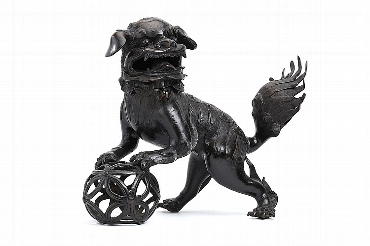 A CHINESE LARGE BUDDHIST LION DOG CENSER.   Ming Dynasty.   Standing, the two front paws resting on the pierced ball, the tail raised, the mouth open for the release of smoke and revealing a mouthful of fierce teeth, the eyes bulging beneath bushy eyebrows and the ears relaxed, the hinged head forming the cover, the figure covered down the back and legs with curling fur, 40cm H.   ? ???????