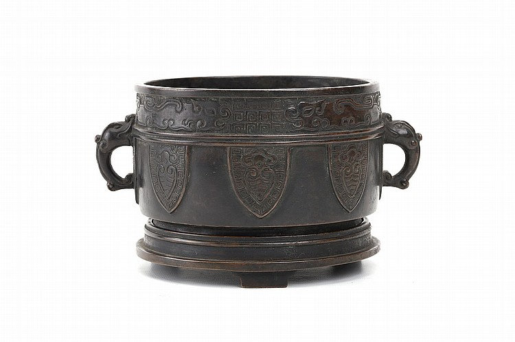 A CHINESE BRONZE CENSER AND STAND. Qing Dynasty. Of cylindrical form the body decorated with a band of archaistic dragons, from which are suspended lappets enclosing stylised cicadas, dragon-form loop handles, the short cylindrical foot supported on