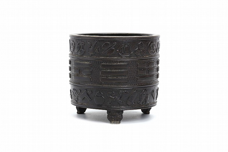 A CHINESE BRONZE CYLINDRICAL 'BAGUA' CENSER.    Ming Dynasty, 17th Century.    Of spherical form, with a central band of eight trigrams separating Buddhist emblems, the short tripod feet formed as animal heads, the base inscribed Hu Wenming zhi to base, 8.5cm H, 9.5cm diameter.   Provenance: Formerly in a European private collection.   ? 17?? ??????
