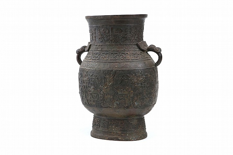 A LARGE CHINESE ARCHAISTIC BRONZE VASE, HU. Ming Dynasty. The compressed pear-shaped body rising from a tall splayed foot to a waisted neck flaring at the rim, flanked by a pair of mythical beast head handles, the body decorated with a band of taotie masks, a similar band on the neck, two further bands of stylised dragons on the shoulders and foot, all reserved on a leiwen ground, 41cm H. ? ?????