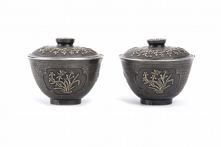 A PAIR OF CHINESE PARCEL GILT SILVER-ALLOY BOWLS AND COVERS. Late Qing Dynasty. The rounded sides decorated with quatrefoil cartouches enclosing raised gilded flowers, the cover decorated with raised gilded blossom, the finials with a gilded circular shou character, unmarked, 7.5cm H. (2) ??? ???????????