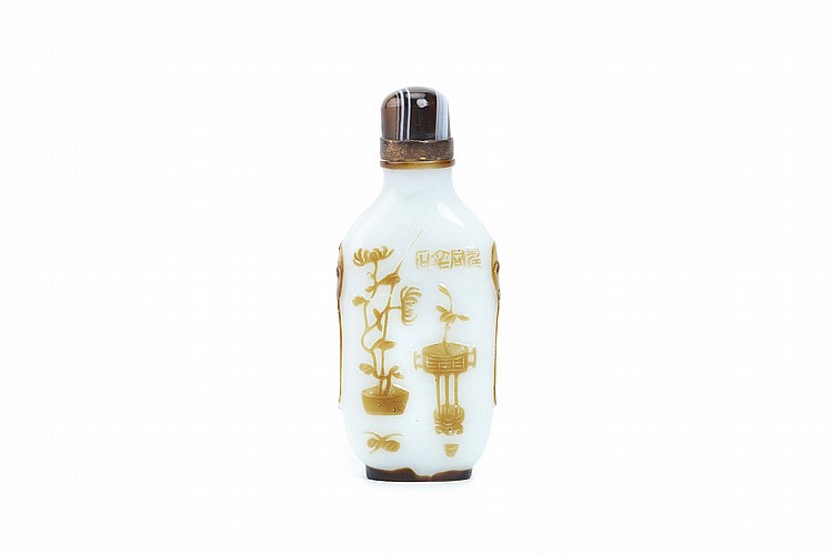 A CHINESE YANGZHOU SCHOOL BROWN OVERLAY GLASS SNUFF BOTTLE. Qing Dynasty. Of flattened rectangular form rising from a short straight oval foot ring, finely carved through the layer of pale brown overlay to the opaque milky white glass, with squirrels and grapes on one side, treasures and flowers on the reverse with an inscription, stopper, 8cm H. Provenance: Collection of P.H. (1926 – 2016). ? ?????????????
