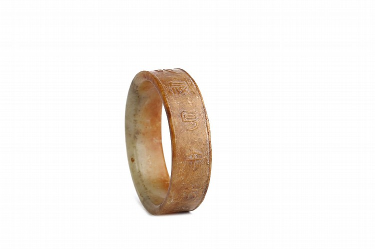 A CHINESE JADE BANGLE WITH INSCRIPTION. Qing Dynasty. The exterior inscribed with characters in seal script between lipped edges, 6cm diameter. Provenance: Collection of P.H. (1926 – 2016). ? ????????