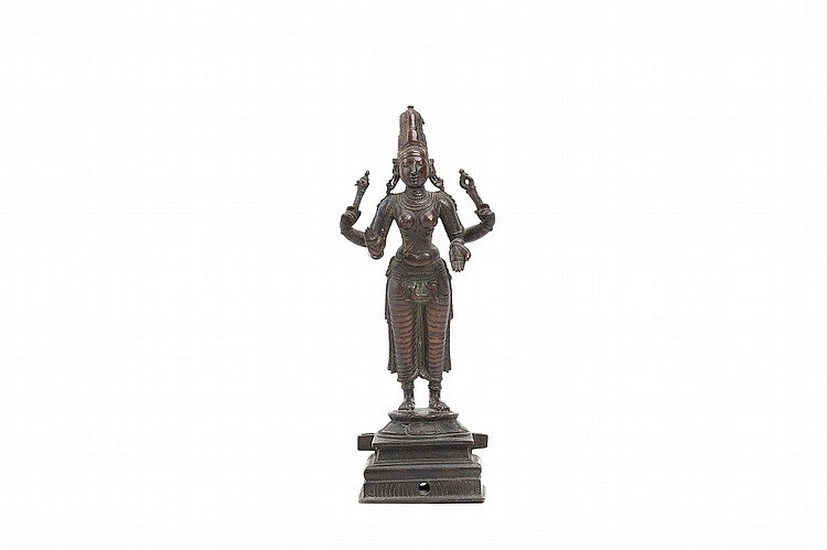 AN INDIAN BRONZE FIGURE OF PARVATI.   16th / 17th Century.   Cast standing on a lotus base, on a rectangular plinth, wearing a long dhoti with sash and further body ornaments, her face flanked by elongated earlobes and surmounted by a tall headdress, 23cm H.   16-17?? ???????