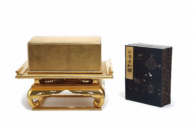 A LACQUER AND GILT SUTRA BOX AND STAND.   19th Century.   A rectangular box containing three volumes of sutra, Sanjo Wasan (Three Buddhist Verses) wood block printed in ink, dated Kaei 1 (1848) resting on a tiered stand with pierced and carved decoration of stylised waves and clouds, in lacquer and gilt, the box 21.5 x 17cm, 22 cm with stand.   ????????????