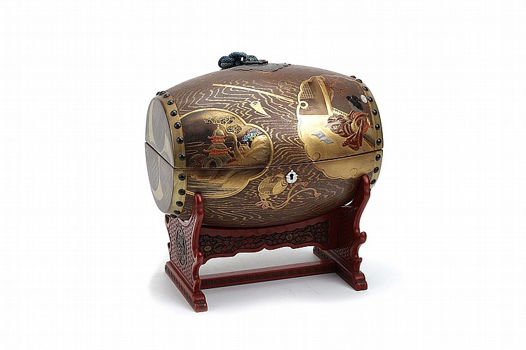 A WOOD AND LACQUER OKIMONO OF A DRUM ON A STAND.   20th Century.   A wood box in the form of a drum decorated in gold and colour lacquer and aogai inlaid with inset pictures of a seated geisha, a pagoda beside a stream, a bamboo garden fence with chrysanthemums, and a bamboo, with a red lacquered wood stand, the drum 31cm x 17cm.   ??????????