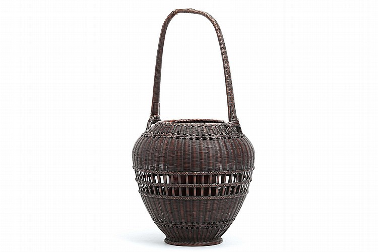 A BAMBOO BASKET BY TANABE CHIKU'UNSAI. 20th Century. A tall ovoid-form Ikebana basket woven in multiple techniques with a loop handle, a bamboo container inside. Signed Chiku'unsai on the base. 43cm H. ?????????????