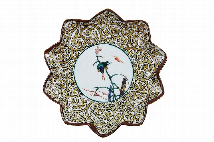 AN ATTRACTIVE KUTANI DISH. Edo period, 18th century. A small lobed dish, decorated in iron-red, blue, green yellow and aubergine and black enamels, with a roundel enclosing a kingfisher perched on reed beside a stream, reserved in stylized karakusa pattern, a mark on the reverse 'fuku', 17cm, D. Literature: A similar dish is illustrated in Susumu Shimazaki, Nippon Toji Zenshu, vol.26 Kutaniyaki, pl no 111. ?? ???????