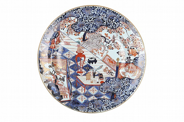 A LARGE IMARI PLATE.   17th Century.   Painted in underglaze-blue, iron-red and gilding with the scholar's objects on a table in a room open to the garden with flowering cherry blossom and nightingales, on the balcony two European dogs seated beside an incense burner, surrounded by stylized clouds with arabesque patterns, 54.5 cm diameter.   ???????????????