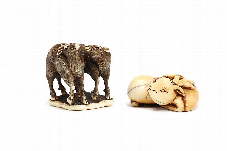 TWO IVORY NETSUKE.   19th Century.   Consisting of an ivory netsuke modelled as a pair of deer, standing with affectionate expressions side by side, well carved and stained details, unsigned, 2.7cm H, together with an ivory netsuke of reclining deer, with its legs folded, unsigned, 3.5cm long. (2)   ????????????