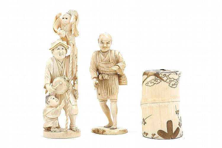 TWO IVORY OKOMONO AND A BOX.   19th / 20th Century.   An ivory okimono of a sarumawashi (monkey trainer), standing holding a long pole and carrying a drum from his neck, a monkey in kimono clambering on to his head, a small boy holding the man's leg, enthusiastically looking at the monkey; a sectional ivory figure of a fisherman; and an ivory container in the shape of a bamboo stem, decorated in gold lacquer with flying cranes and pine tree. (3)   ???????????????