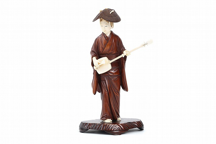 AN IVORY AND WOOD OKIMONO OF A TRAVELLING MUSICIAN.   Meiji period.   Possibly representing Goze (blind musician), the woman is shown outdoors, wearing her straw hat, playing the shamisen as she walks. Her face and coiffure elegantly carved and detailed with ink and slight colour, her kimono inlaid with mother-of-peal mon of a stylised flower petals, wood stand, 27cm H.   ???????????????