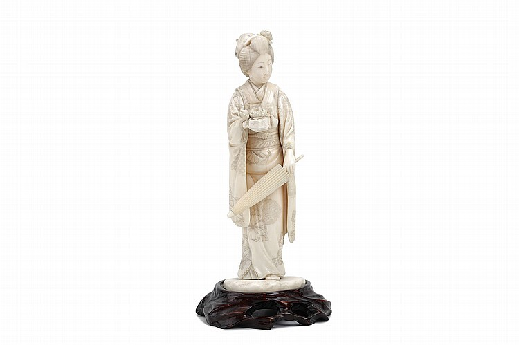 AN IVORY OKIONO OF A BEAUTY. Meiji period. Standing with a folded umbrella in her right hand, holding a ryoshibako (letter box) in the right hand, elegantly dressed in her fine kimono decorated with floral pattern, a spray of flowers on her hair, 27cm H.