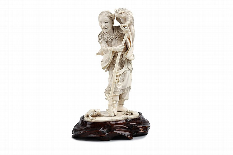 A FINE IVORY OKOMONO OF A CHINESE IMMORTAL.   Meiji period.   Carved as Gama Sen'nin, the Toad Immortal, standing and holding his staff whilst a large toad clambers over his shoulder, wood stand, 23cm H.    ???????????????