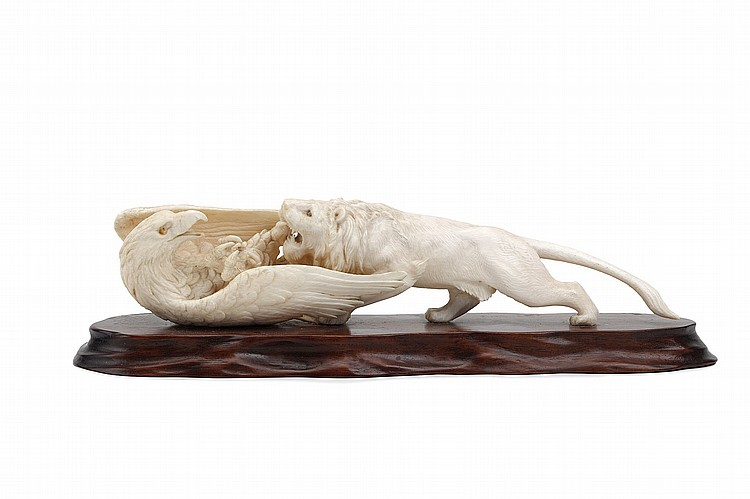AN IVORY GROUP OF LION AND A HAWK.   19th / 20th Century.   Well carved with inlaid eyes, a large bird of prey protecting itself from a male lion, with fitted wood stand, 28cm L.   ????????????????????