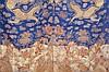 A CHINESE EMBROIDERED BLUE GROUND DRAGON ROBE.   Qing Dynasty.   Decorated in gold thread with four-clawed dragons among clouds, flames and auspicious objects, above waves, 136cm H, 180cm across.   ? ????
