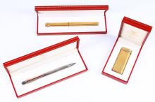 CARTIER     A gold plated Cartier cigarette lighter (boxed), sold together with a gold plated Cartier ball point pen with ribbed body (boxed) and a Must de Cartier silver propelling pencil (boxed), all having the signature tri-colour gold collars. (3)