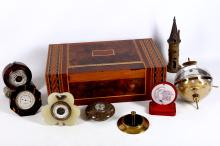 A collection of five desktop barometers and thermometers, to include examples in marble, faux tortoiseshell and onyx; together with a German globe barometer / hygrometer, one other modelled as a tower, and a Swiss parquetry inlaid box (8)