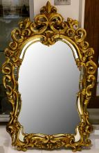 A large giltwood Rococo style mirror, with an elaborate scroll-moulded frame, 141 x 89cm