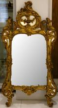 An attractive giltwood Rococo style mirror, with a scroll-moulded frame, 132 x 69cm