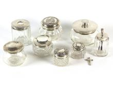 A silver mounted jar, the cover Levi & Salaman, Birmingham 1905, decorated a Classical figure, and seven other silver mounted glass jars various