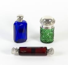 A double-ended red glass scent bottle, with engraved white metal covers, a blue scent bottle with silver mount and a green glass jar with silver cover