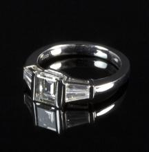 An emerald cut diamond solitaire ring, approximately 1ct, flanked with tapering baguette cut diamond shoulders to a platinum setting, stamped PT 950, size N½