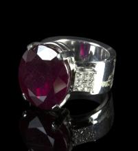 A ruby and diamond dress ring, the central oval cut ruby of approximately 20ct with a grid of princess cut diamonds to each shoulder, the 18k white gold shank marked for Charnet, Paris, size approximately M/L