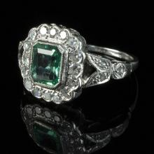 A Colombian emerald and diamond cluster ring, the emerald of approximately 1.99ct to a surround of diamonds and split shoulders, set in 18ct white gold and platinum, size P, with certificate