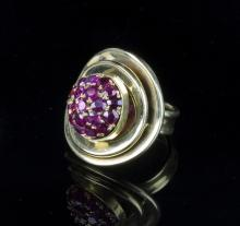 An 18ct gold and ruby dress ring of modern design, the domed ruby set centre to concentric gold borders, size N
