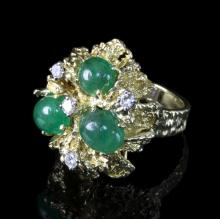 An Alan Gard ring of modern design, set with three cabochon emeralds and four diamonds to a textured 18ct gold setting, size M