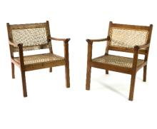 A pair of 20th Century Danish style beechwood framed open armchairs, each with caned back and seat