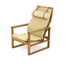 An oak framed reclining armchair, possibly Danish with caned seat and leather strapped calico seat cushion