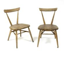 A pair of Ercol stacking school chairs in elm and beech, one with Ercol stamp and ink patent stamps beneath