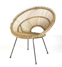 A 1970s style canework chair, the woven openwork frame of sunburst design on a metal base with four splay legs