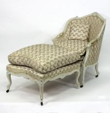 A French painted tub chair, the moulded scrolling frame on carved legs with castors and the matching footstool