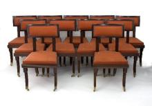 A set of eleven mahogany dining chairs, each with reeded column back supports, sides and sabre legs, upholstered in deep orange horse hair fabric, on brass castors and caps/Provenance: George Spencer Designs
