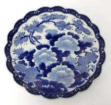A Japanese blue and white charger, decorated flowering branches and with a lobed border, 46cm diameter