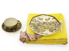 A Japanese satsuma octagonal plate, 19th Century, decorated deities, 20.5cm wide, a satsuma cup and saucer and an embroidered scroll holder with dragon decoration