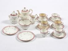 A child's porcelain tea set decorated blue and puce to a white ground