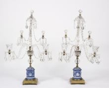 A pair of Regency cut glass table lustres in the style of William Parker, with central tapered column and inverted sconce hung festoons of drops, above four faceted scroll branches, two with similar festoons and two with nozzles, raised on cylindrical Wedgwood vase-shaped supports, 83cm high overall/see illustration