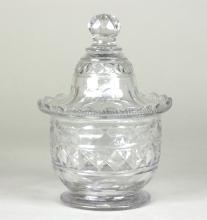 A small Irish glass lidded jar, cut with ovals and diamonds, 14.5cm high