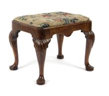 A George I walnut stool, with carved acanthus to the knees on cabriole legs with pad feet, fitted a loose trap needlework seat, 53cm wide /see illustration
