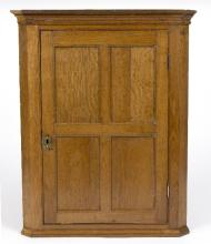 An early 19th Century oak hanging corner cupboard with four-panel door, 88cm x 71cm