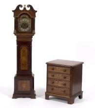 A miniature longcase clock case, 89cm high and a mahogany chest of four drawers, 30cm wide