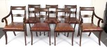 A set of Regency mahogany dining chairs with cable carved top rails above pierced and carved horizontal splats, fitted loose trap seats and raised on plain sabre front legs, comprising five single chairs and two armchairs