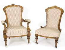 A late Victorian pair of fireside chairs, on turned front legs