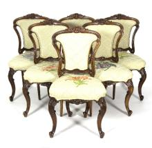 A set of six carved walnut framed salon chairs, with upholstered backs and seats on moulded cabriole front legs with knurl feet